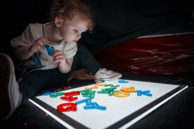 We offer learning opportunities and support for families, vital to every child with visual impairments and other complex needs during their earliest years of development. Image shows baby looking at letters. Early Years group
