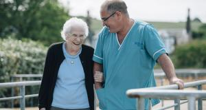 A resident and staff member stand arm in arm on the roof terrace at Braeside House
