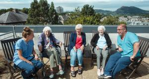 A group of residents and staff sit in a semi circle on the roof terrace at Braeside House