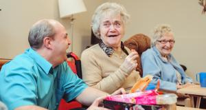 Two residents laugh with a Braeside House staff member