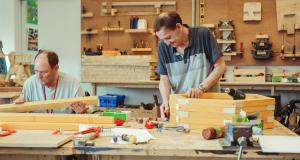 Two veterans work on wood work projects in the Linburn Centre workshop
