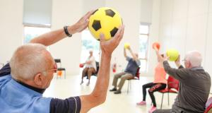 Veteran throws ball to group in strength and balance class at Linburn Centre