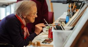 veteran with sight loss paints in the Linburn Centre art room