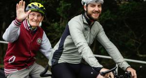 Veteran waves while tandem cycling with Vie Velo at Linburn Centre