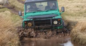 Veterans drive through mud in a 4x4 offraod driving activity
